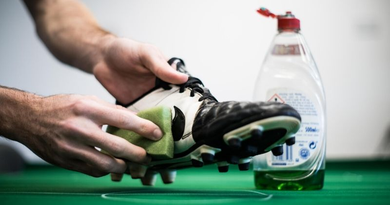 scrubbing muddy football boots clean with soap
