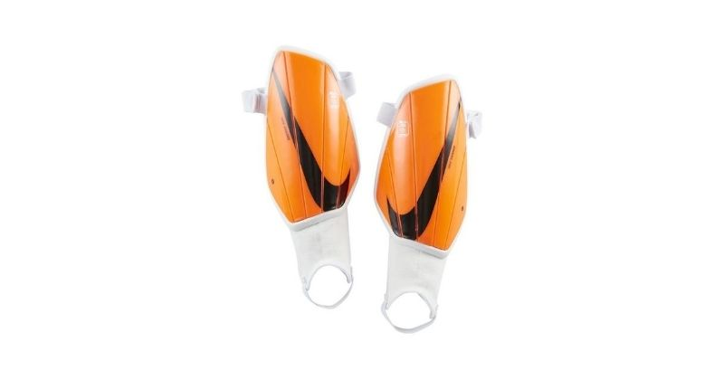 orange nike charge shin pads with stirrup fastening