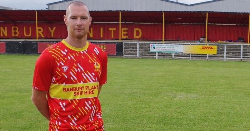 player modelling the red banbury united home kit