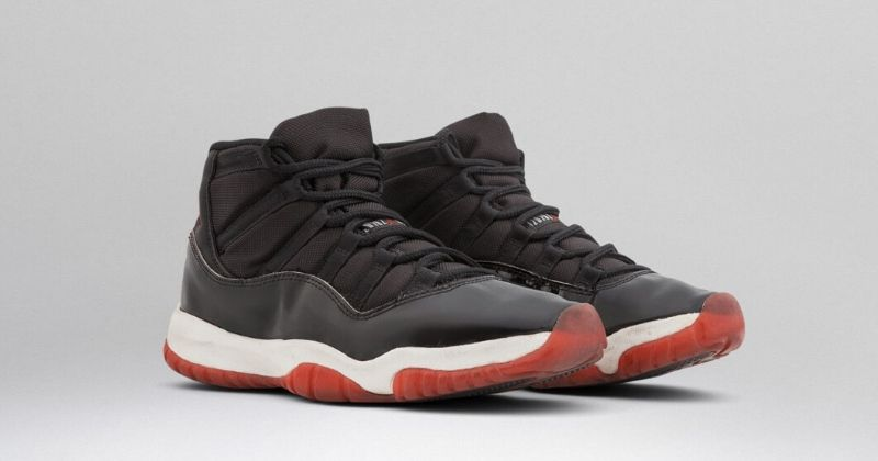 1995 Nike Air Jordan 11 in black with red and white sole on light background