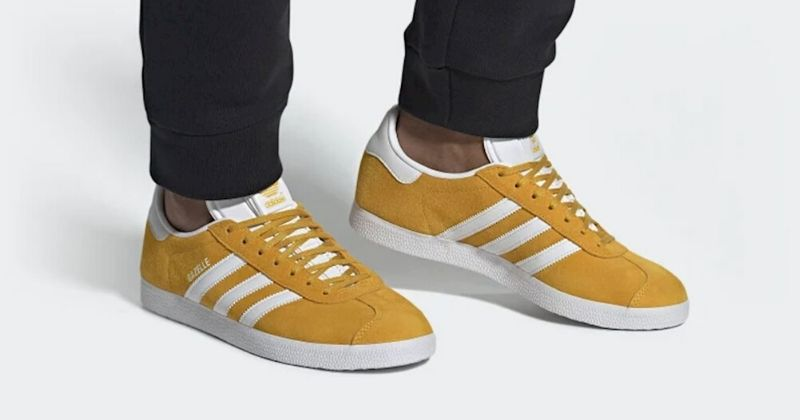 Person wearing yellow and white adidas Gazelle on a white background