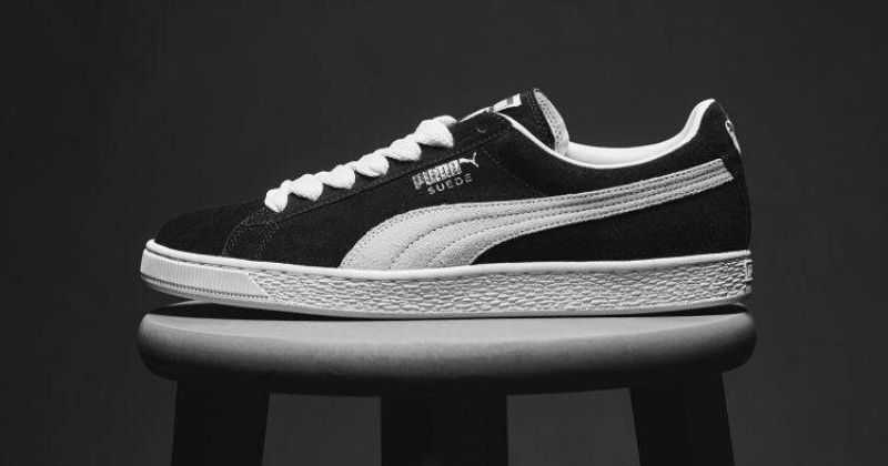 Puma Suede in black and white on a stool against a dark background