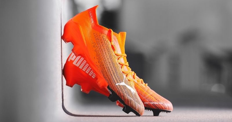 puma ultra football boots in orange on grey street